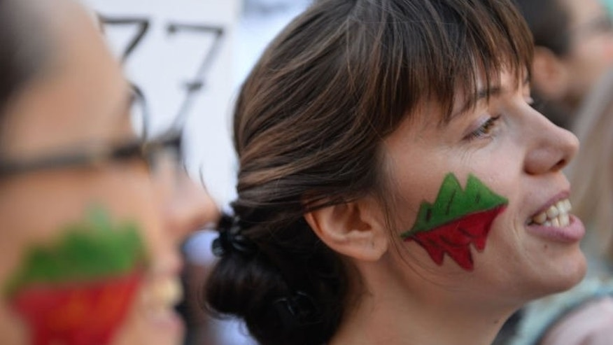 """Protesters have their faces painted with the """"Save Rosia Montana"""" logo on September 15, 2013 in Bucharest."""