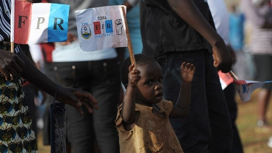 A child holds a party flag as supporters of the Rwandan President and the ruling Rwandan Patriotic Front (RPF) party attend a campaign rally in the capital Kigali on September 14, 2013.