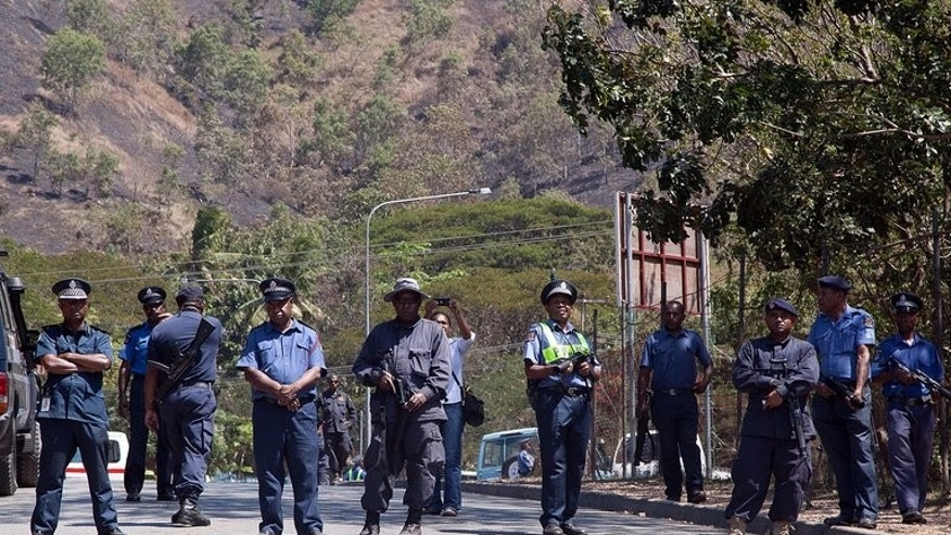PNG police look on at a student march in Port Moresby on August 2, 2013. A third man died of his injuries following an ambush on foreign trekkers in Morobe province.