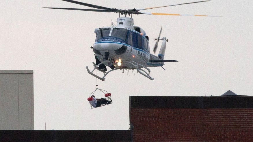 A U.S. Park Police helicopter removes a man in a basket from the Washington Navy Yard Monday, Sept. 16, 2013.