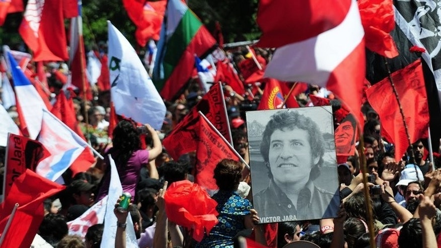 People hold the portrait of Chilean singer Victor Jara, during his funeral in Santiago on December 5, 2009.