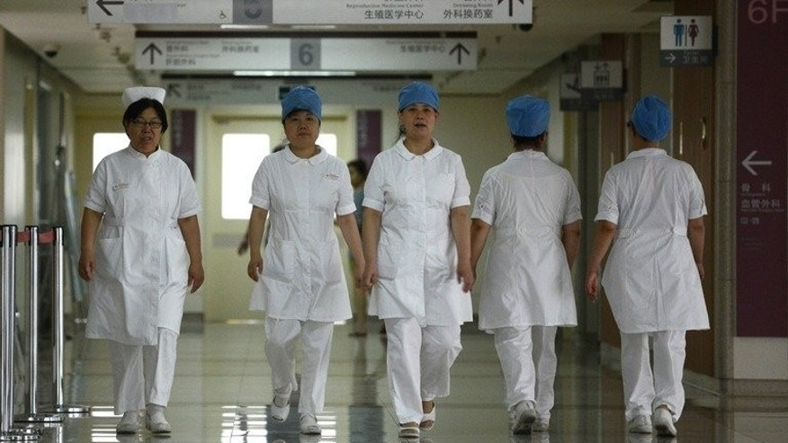 Illustration: a group of nurses walks along a corridor at a hospital in Beijing on July 29, 2013.