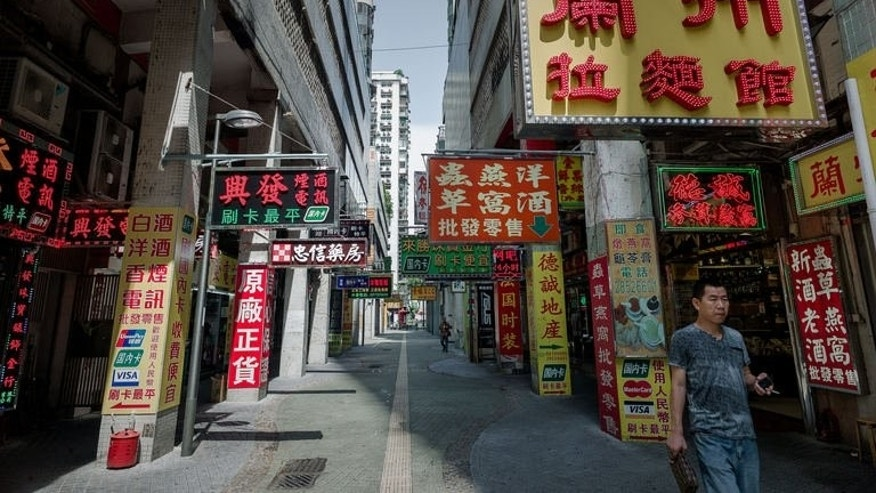 A man walks past shops in the Chinese gambling enclave of Macau, September 11, 2013.