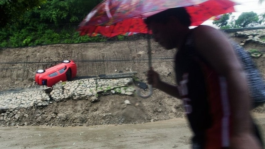 A passer-by walks near a car that fell after part of a hill collapsed in Acapulco, in Mexico's Guerrero state, on September 15, 2013. Hurricane Ingrid has weakened to a tropical storm as it crossed Mexico's northeastern coast, one day after 21 people died when another storm struck the opposite side of the country.