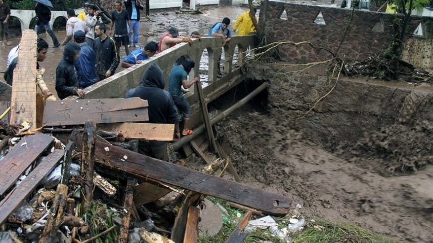 xican civilians try to repair a broken bridge in Chilpancingo, Guerrero state, on September 15, 2013. Hurricane Ingrid has weakened to a tropical storm as it crossed Mexico's northeastern coast, one day after 21 people died when another storm struck the opposite side of the country.