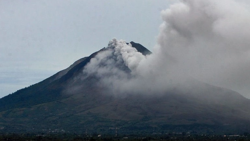 Mount Sinabung spews thick smoke and ash in Indonesia's Karo district on North Sumatre province, on September 15, 2013. Nearly six thousand people have fled their homes on Indonesia's Sumatra island after a huge volcanic eruption at the weekend, as the volcano continued to belch out more smoke.