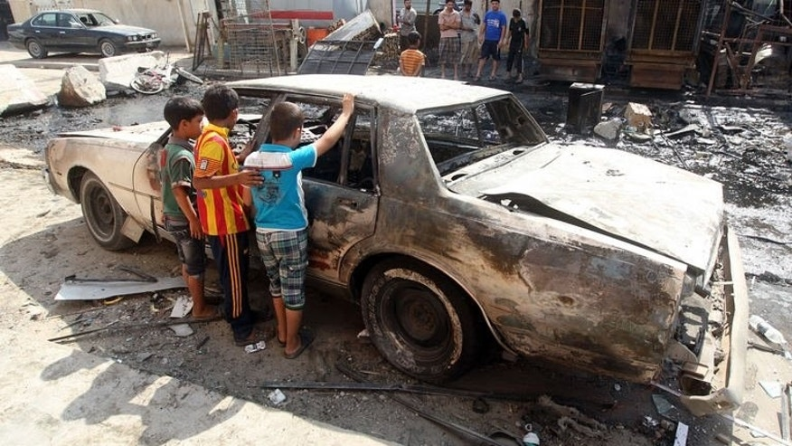 Iraqi children inspect a burnt-out car at the site of a car bomb attack that exploded the previous day in a commercial street of Baghdad's eastern neighbourhood of Mashtal on September 16, 2013.