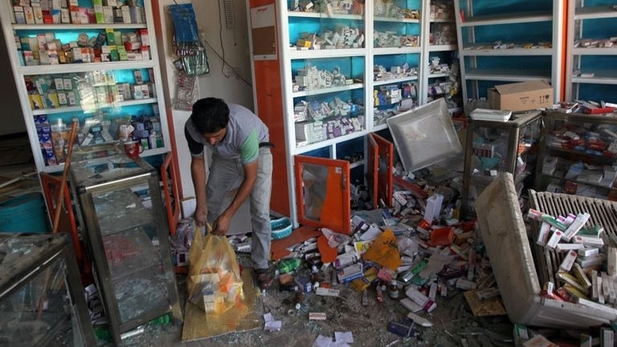 An Iraqi pharmacist clears up the damage following a car bomb explosion the previous day in a commercial street of Baghdad's eastern neighbourhood of Mashtal on September 16, 2013.