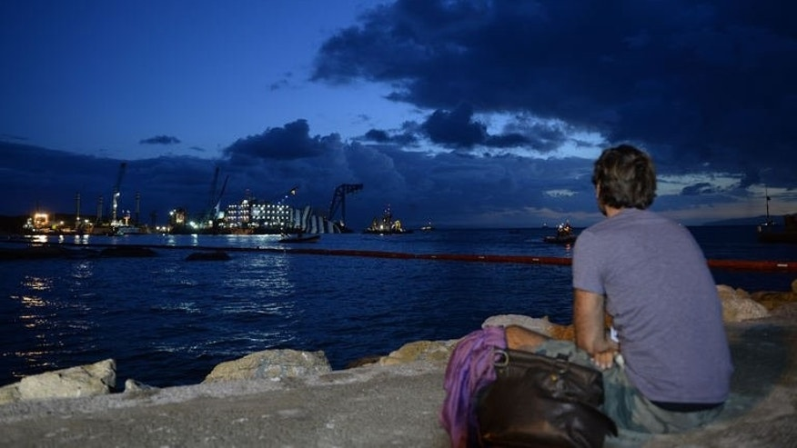 A man watches as work crews prepare to raise the wreck of Italy's Costa Concordia cruise ship near the harbour of Giglio Porto, early on September 16, 2013.