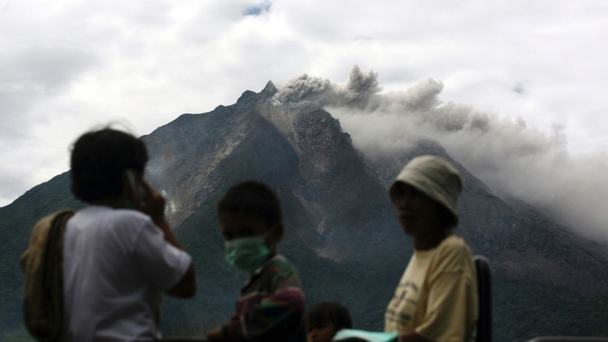Sept. 15, 2013 - Mount Sinabung spews volcanic materials as villagers board a truck to flee their homes following its eruption in Karo, North Sumatra, Indonesia. Thousands of people have been evacuated from their homes after the volcano erupted early Sunday.