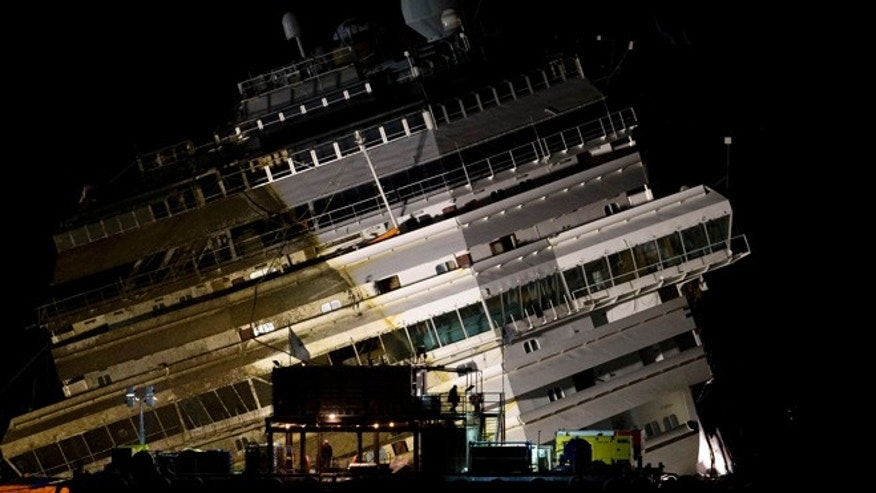 Sept. 17, 2013: The Costa Concordia lies on its side on the Tuscan Island of Giglio, Italy, early Tuesday morning. Using a vast system of steel cables and pulleys, maritime engineers on Monday gingerly winched the massive hull of the Costa Concordia off the reef where the cruise ship capsized in January 2012 and are poised to set it upright.