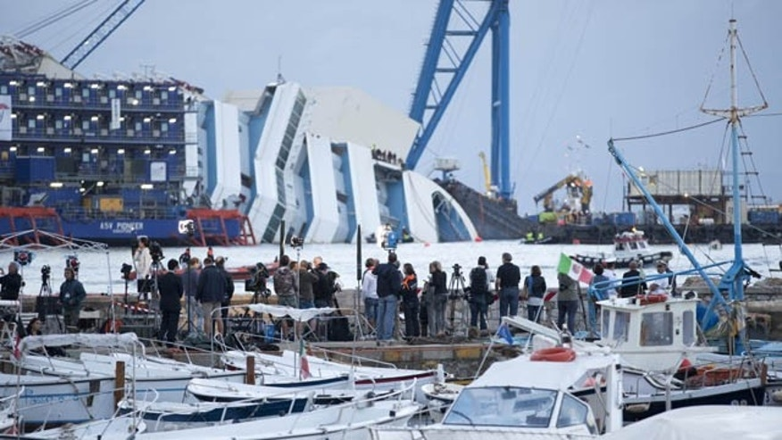 September 16, 2013: Reporters watch the Costa Concordia ship lying on its side on the Tuscan Island of Giglio, Italy. An international team of engineers is trying a never-before attempted strategy to set upright the luxury liner, which capsized after striking a reef in 2012 killing 32 people. (AP Photo)