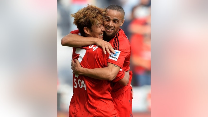Leverkusen striker Son Heung-Min (L) and teammate Sidney Sam celebrate during their Bundesliga match against Freiburg in western Germany on August 10, 2013.