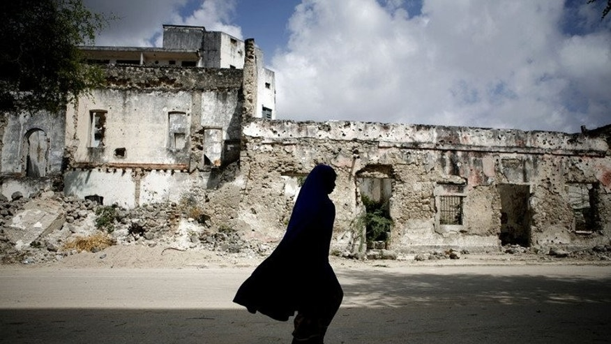"A Somali woman walks on a street in Mogadishu December 12, 2007. International donors began work on a ""New Deal"" for Somalia to drive its economic and political recovery after two decades of bloody civil war."