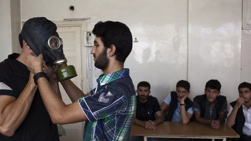 Former student Mohammad Zayed (2L) shows fellow Syrians how to put on gas masks in Aleppo on September 15, 2013. Zayed, a former student at Homs University, dedicates his days to teaching volunteers how to help people cope with a chemical weapons attack -- just in case.