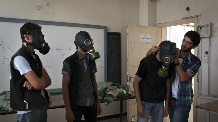 Former student Mohammad Zayed (R), shows fellow Syrians how to put on gas masks in Aleppo on September 15, 2013. Zayed, a former student at Homs University, dedicates his days to teaching volunteers how to help people cope with a chemical weapons attack -- just in case.