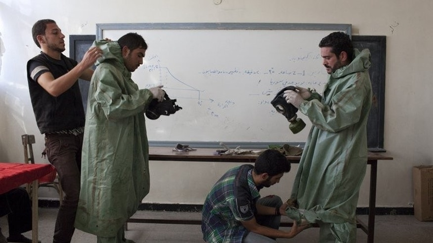 Former student Mohammad Zayed (2R) shows fellow Syrians how to put on protective gear, in Aleppo on September 15, 2013. Zayed dedicates his days to teaching volunteers how to help people cope with a chemical weapons attack -- just in case.