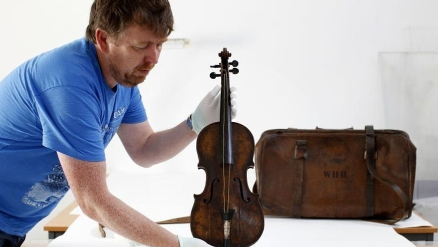The violin played by bandmaster Wallace Hartley during the final moments before the sinking of the Titanic is displayed by conservator Sean Madden at his studio in Lurgan, Northern Ireland, on September 16, 2013. The violin is to go on display at a museum marking the tragedy in Northern Ireland, officials said Monday.