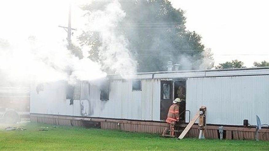 Firefighters extinguish a mobile home fire Sunday, Sept. 15, 2013, that killed a man and five children in Tiffin, Ohio.