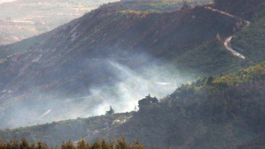 Sept. 16, 2013 - Smoke rises from the Syrian side of the border after a Turkish air force jet downed a Syrian military helicopter at the Turkey-Syria border near Hatay province.