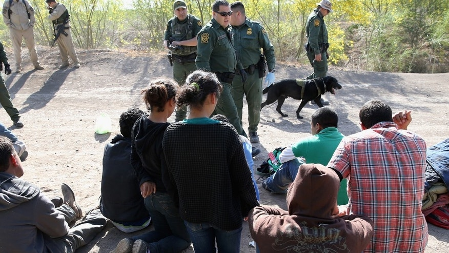 U.S. Border Patrol and U.S. Air and Marine agents detain undocumented immigrants near the U.S.-Mexico border on April 11, 2013 near Mission, Texas.