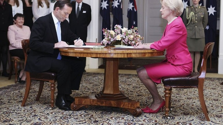Tony Abbott (L) is sworn in as the 28th prime minister of Australia by Governor-General Quentin Bryce (R) during a ceremony in Canberra on September 18, 2013.