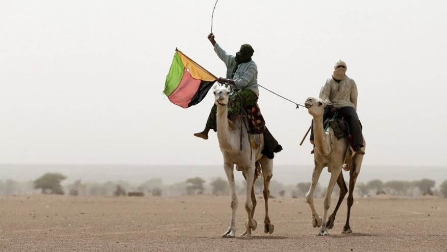 A Tuareg man holds the flag of the National Movement for the Liberation of Azawad (MLNA) during a demonstration in Kidal, northern Mali on July 28, 2013. Armed factions from Mali's diverse and bitterly-opposed desert communities have committed to peace talks to end an 18-month crisis triggered by a Tuareg uprising.