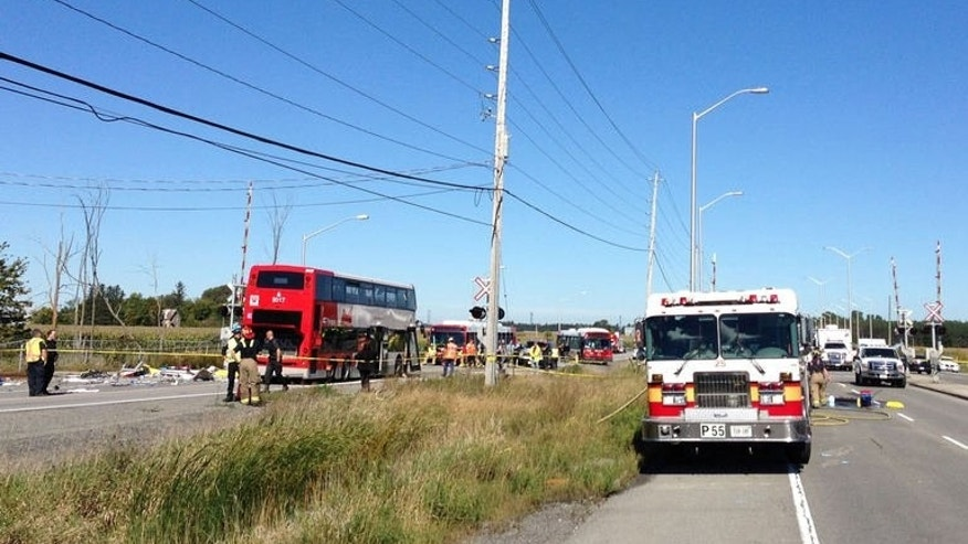 A double-decker bus is viewed after it collided with a passenger train at a crossing in a suburb of Canada's capital on September 18, 2013.