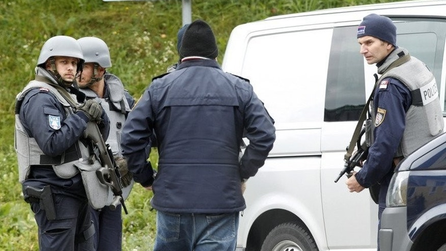 Austrian armed police block a road near Grosspriel, on September 17, 2013. Austrian prosecutors have said a poacher who killed three policemen and a paramedic most likely died after shooting himself in the head.