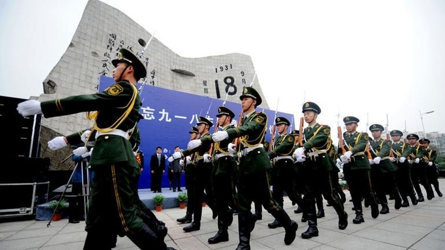 "An honor guard marches in front of the September 18th History Museum as soldiers, the armed police and citizens gather on the square to commemorate the 82nd anniversary of the ""Mukden Incident"" in Shenyang, northeast China's Liaoning province on September 18, 2013."