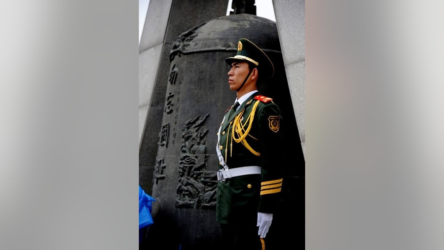 "A soldier from People's Liberation Army stands beside a bell carved with words saying, ""Never Forget National Humiliation"", as soldiers, the armed police and citizens gather on the square before the September 18th History Museum to commemorate the 82nd anniversary of the ""Mukden Incident"" in Shenyang, northeast China's Liaoning province on September 18, 2013."