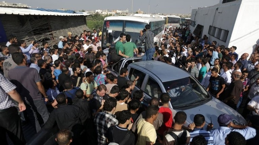 "Palestinians surround buses crossing the Rafah border during a brief opening on September 18, 2013, as they protest against the ""indefinite"" closing by Egyptian authorities of the crossing."