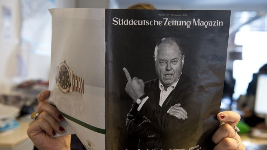 "A woman holds a magazine supplement of Sueddeutsche Zeitung depicting Peer Steinbrueck giving the middle finger on September 13, 2013. Angela Merkel's necklace, a middle-finger photo and ""Veggie Day"" have been hot-button issues in a general election campaign that Germans say has been shockingly banal."