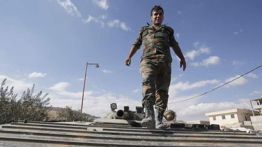 A soldier in the Syrian army walks on the top of a Russian-made armoured personnel carrier in Maalula on September 18, 2013.