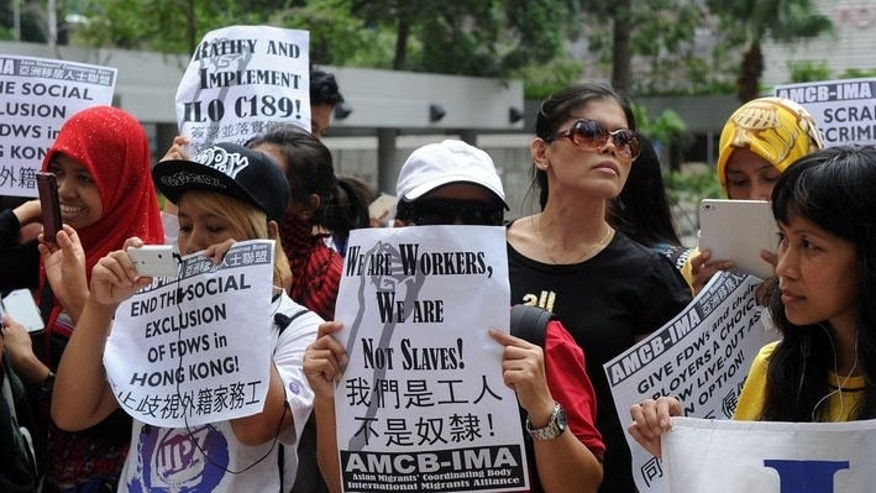 Members of the Asian Migrants Coordinating Body hold a protest outside a court where a local couple stands trial for abusing their Indonesian domestic helper in Hong Kong on September 18, 2013.