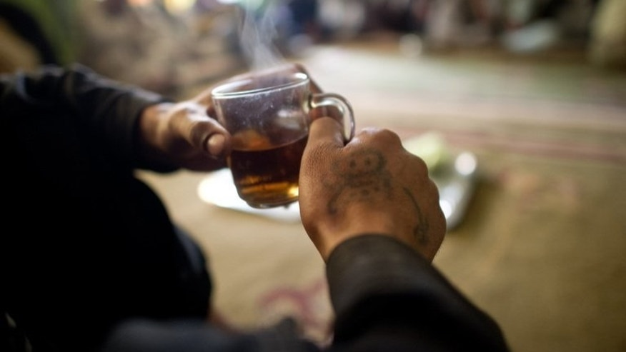 "A man drinks tea in Kabul on April 24, 2012. An Indian court has reprimanded police for arresting a man they accused of drinking tea in a ""suspicious"" manner at one of the country's ubiquitous roadside stalls."