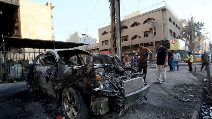 Iraqi men inspect the wreckage of a car at the site of a car bomb explosion in central Baghdad on September 18, 2013.