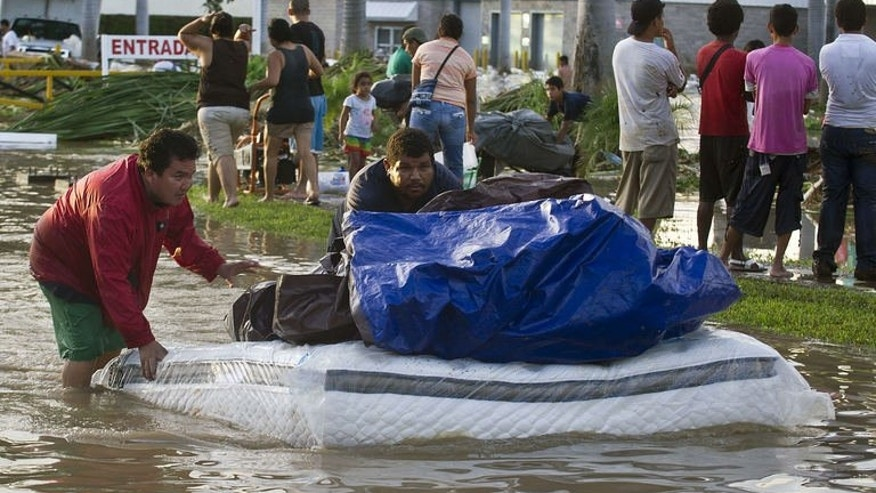 Looters flee with goods from a supermarket in Acapulco, state of Guerrero, Mexico, on September 17, 2013 as heavy rains hit the country.