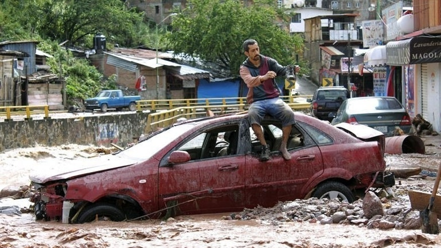A man sits atop a car while trying to cross a flooded street in Chilpancingo, state of Guerrero, Mexico, on September 17, 2013.