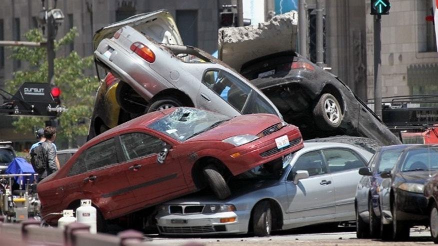 "Workers stage a car accident during the filming of the movie ""Transformers 3"" in Chicago, Illinois."