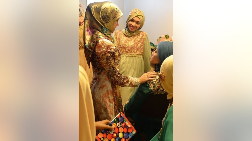 Muslimah World pageant contestant Dayangku Rabiatul Adawiyah (L) of Brunei talks to other contestants while they prepare backstage for the grand final of the contest in Jakarta on September 18, 2013. The finale of a beauty pageant exclusively for Muslim women will take place in the Indonesian capital Wednesday, in a riposte to the Miss World contest in Bali that has drawn fierce opposition.
