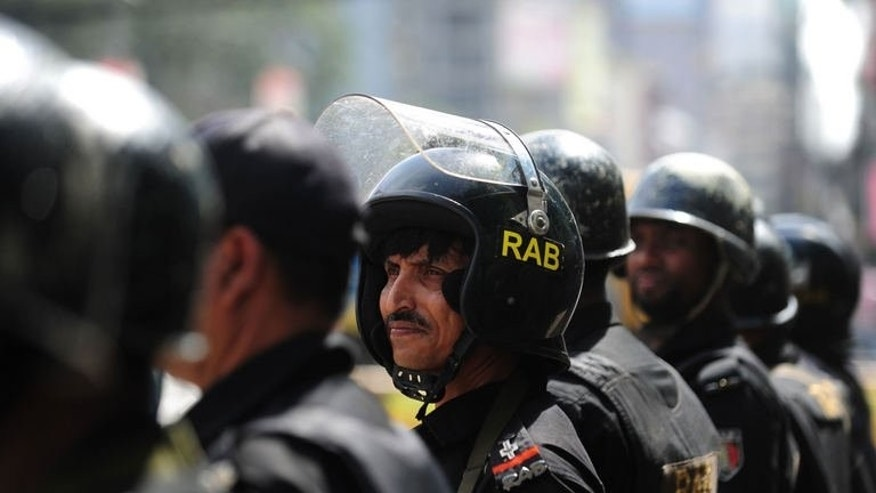 Bangladeshi Rapid Action Battalion personnel stand guard during a nationwide strike called by Islamist political party, Bangladesh Jumaat-e-Islami, to protest against death sentenced of its leader Abdul Quader Molla in Dhaka on September 18, 2013.