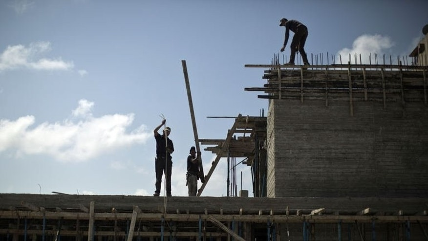 Palestinian construction labourers work at a construction site in Gaza City on September 18, 2013.