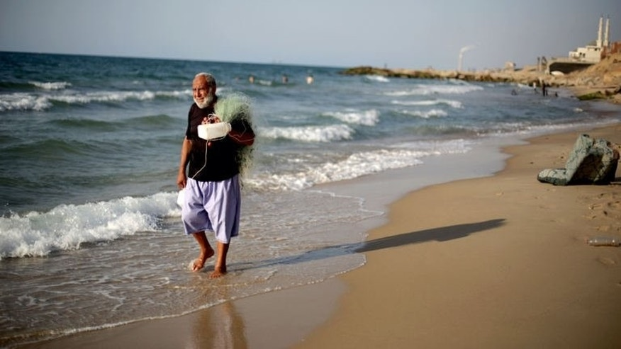 A Palestinian man carrying a fish net walks on the beach in the Shati refugee camp in Gaza City on September 13, 2013.