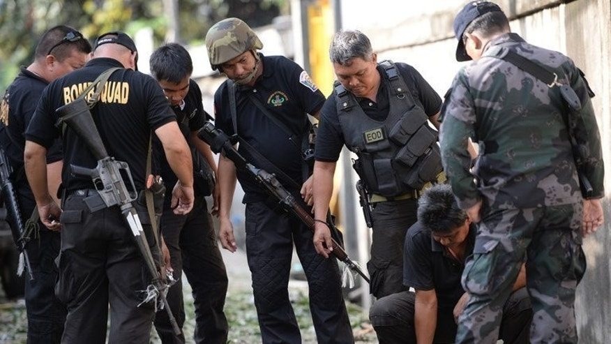 Philippine police officers and soldiers look for evidence after a car bomb in Zamboanga, on September 16, 2013. Philippine soldiers are pursuing heavily armed Muslim rebels through the streets and homes of a major city, warning they would be killed or captured unless they surrendered.