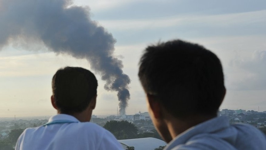 Two men watch as smoke billows from burning houses in Zamboanga City, on September 16, 2013. Philippine soldiers are pursuing heavily armed Muslim rebels through the streets and homes of a major city, warning they would be killed or captured unless they surrendered.