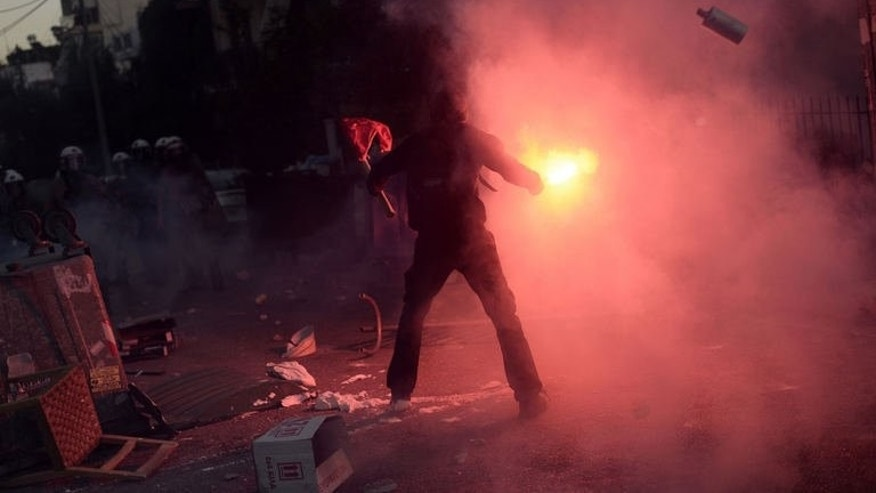 A Greek protester lights a flare during clashes with riot policemen in Athens on September 18, 2013.