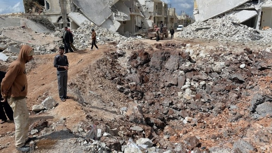 People walk past destroyed houses in the northern Syrian town of Azaz on April 21, 2013.