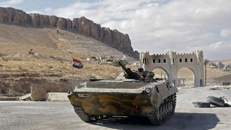 A Russian made Syrian armoured personnel carrier roles along a street leading into Syria's ancient Christian town of Maalula on September 18, 2013.