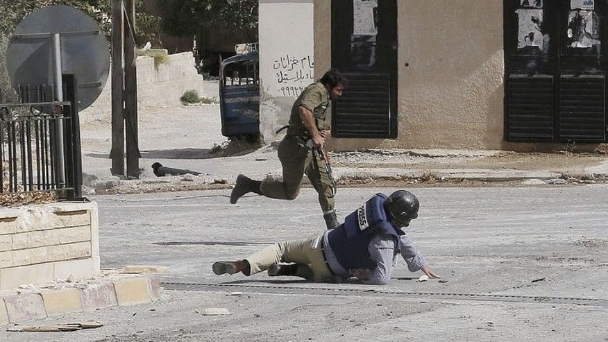 AFP reporter Sammy Ketz, hits the ground as a Syrian soldier runs past during snipper fire in the ancient Christian town of Maalula, on September 18, 2013.